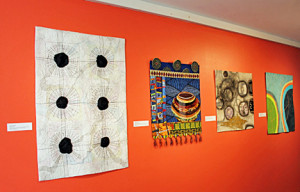 Installation photo of Art as Quilt: Transitions in Contemporary Textile Media at the Fuller Craft Museum. Pictured (left to right) are works by Sharyn L. Raiche, Janice M. Jones, and Sandra T. Donabed.